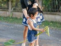 Weinig Aziatisch babymeisje, met hulp van haar moeder, die bereid om het hobbelpaard die van de Banaanrib te spelen kluay Ma beri stock foto