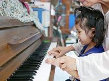 Weinig Aziatisch babymeisje wat betreft een piano voor het eerst in haar leven stock afbeeldingen