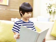 Weinig Aziatisch boek van de jongenslezing thuis stock foto
