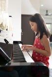 Weinig Aziatisch meisje bij piano royalty-vrije stock afbeelding