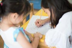 Weinig Aziatisch meisje die in de notitieboekjeschool schrijven royalty-vrije stock foto's