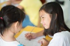 Weinig Aziatisch meisje die in de notitieboekjeschool schrijven stock foto's