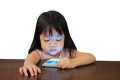 Weinig Aziatisch meisje die op mobiele telefoon op witte achtergrond letten met Royalty-vrije Stock Afbeeldingen