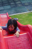 Weinig Aziatisch meisje die op schuif spelen stock afbeelding