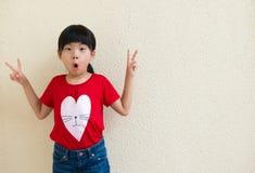 Weinig Aziatisch meisje die overwinningshand tonen Stock Fotografie