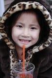 Weinig Aziatisch meisje met kap het drinken Stock Afbeeldingen