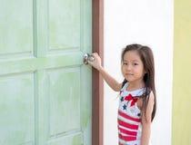 Weinig Aziatisch meisjesjong geitje probeert om de deur te openen Royalty-vrije Stock Fotografie
