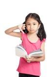 Weinig Aziatisch ongelukkig meisje toont duimen neer gelezen een boek royalty-vrije stock fotografie