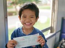 Weinig Aziatische baby die een treinkaartje in haar handen met grote gelukkige glimlach houden terwijl zij door trein voor het ee stock afbeelding
