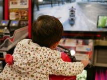 Weinig Aziatische baby geniet van berijdend een spel van de arcademotorfiets royalty-vrije stock foto's