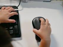 Weinig Aziatische baby` s handen op een computermuis stock fotografie