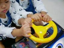 Weinig Aziatische babymeisjes, siblings, die een stuurwiel van een arcadespel delen stock foto