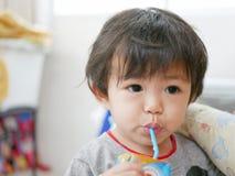 Weinig Aziatische consumptiemelk van het babymeisje van een melkkarton zelf royalty-vrije stock foto