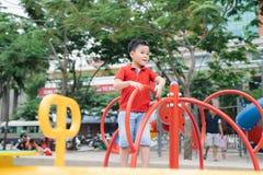 Weinig Aziatische jongen die een schommeling berijden en verheugt zich stock foto