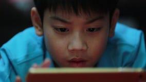 Weinig Aziatische jongen die op de spelen van de tabletcomputer spelen stock videobeelden