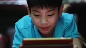 Weinig Aziatische jongen die op de spelen van de tabletcomputer spelen stock video