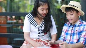 Weinig Aziatische jongen met mobiele telefoon en tiener spreken samen stock videobeelden