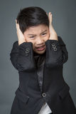 Weinig Aziatische jongen in zwart verstoord kostuum, depressiegezicht Royalty-vrije Stock Afbeeldingen