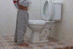 Weinig Aziatische jongensurine in het toilet stock foto