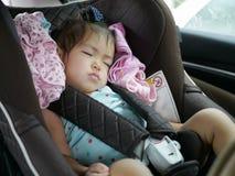 Weinig Aziatische slaap van het babymeisje op een autozetel voor babyveiligheid royalty-vrije stock afbeeldingen