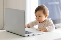 Weinig baby bekijkt aandachtig het scherm van laptop voor hem, die met computer werken royalty-vrije stock fotografie