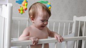 Weinig baby bevindt zich en schreeuwt in een babyvoederbak, trekt de pennen stock footage