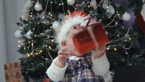 Weinig baby in de spelen van de Kerstmanhoed met een gift stock video
