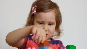 Weinig baby die met kleurrijke kleine blokken van een aannemer spelen Het kind ontwikkelt zijn het denken en motorvaardigheden A stock video