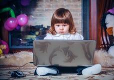 Weinig baby die met laptop spelen Stock Foto's