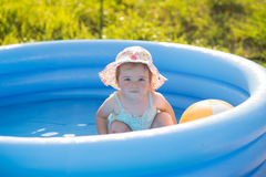 Weinig baby die met speelgoed in opblaasbare pool spelen stock afbeelding