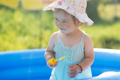 Weinig baby die met speelgoed in opblaasbare pool spelen stock fotografie