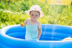 Weinig baby die met speelgoed in opblaasbare pool spelen stock foto