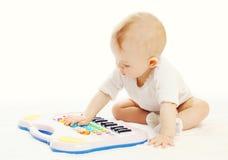 Weinig baby die met stuk speelgoed piano op een wit spelen Royalty-vrije Stock Afbeeldingen