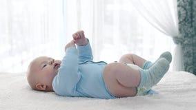 Weinig baby die op een rug liggen stock videobeelden