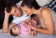 Weinig baby die op het bed met zijn ouders liggen Stock Foto's
