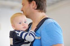 Weinig baby in een babydrager Stock Foto's