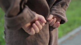 Weinig baby in een bruin linnen jumpsuit houdt zijn handen achter zijn rug stock footage