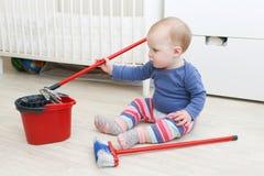 Weinig baby 10 maanden doet thuis het schoonmaken Stock Foto's