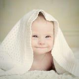 Weinig baby met Benedensyndroom verborg slyly onder deken en glimlachen Royalty-vrije Stock Foto's