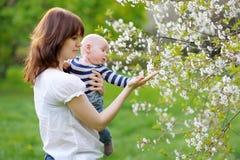 Weinig baby met haar moeder in de tuin Stock Afbeeldingen