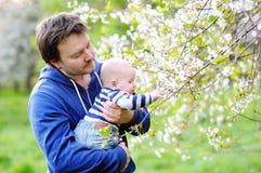 Weinig baby met vader in de bloesemtuin stock foto