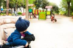 Weinig baby op wandelwagen die spelen in stadstuin bekijken stock afbeeldingen