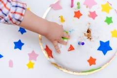 Weinig baby raakt zijn verjaardagscake die op de lijst ligt Royalty-vrije Stock Fotografie