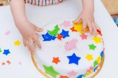 Weinig baby raakt zijn verjaardagscake die op de lijst ligt Stock Fotografie