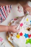 Weinig baby raakt zijn verjaardagscake die op de lijst ligt Royalty-vrije Stock Foto's