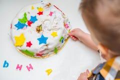 Weinig baby raakt zijn verjaardagscake die op de lijst ligt Royalty-vrije Stock Afbeeldingen