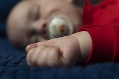 Weinig baby sleepingon op een blauwe handdoek stock afbeeldingen