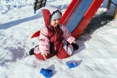 Weinig baby speelt in de speelplaats in de winter Stock Foto's
