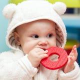 Weinig babybaby kauwt op een zacht plastic stuk speelgoed Royalty-vrije Stock Fotografie
