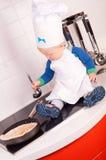 Weinig babychef-kok in de kokhoed die pannekoeken maakt Royalty-vrije Stock Afbeelding